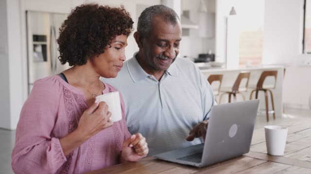 Senior black man and his middle aged daughter using a laptop together at home, close up