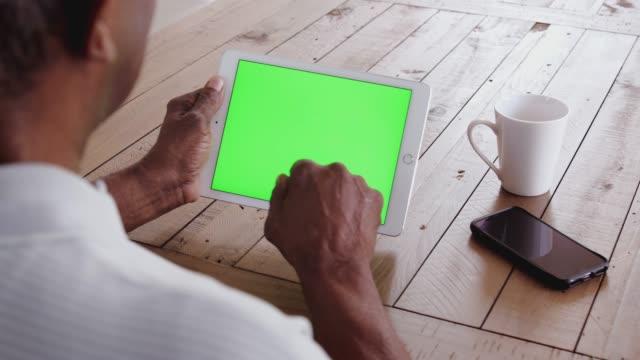 uomo di colore anziano a un tavolo usando un tablet orizzontalmente, sopra la vista della spalla, primo piano - braccio umano video stock e b–roll