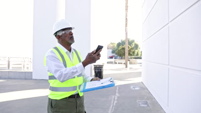 Senior Black Man Construction Manager Inspection A senior black male construction site manager visually inspects a building project quality control stock videos & royalty-free footage