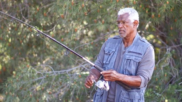 senior black man fishing - łowić ryby filmów i materiałów b-roll