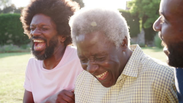 Senior black man laughing with his two adult sons, close up Senior black man laughing with his two adult sons, close up adult stock videos & royalty-free footage