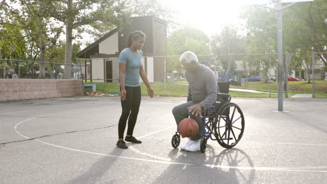 senior black man playing basketball with daughter in wheelchair - rispetto video stock e b–roll