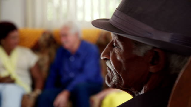 senior black man with hat looking at camera in hospice - senior care stock videos and b-roll footage