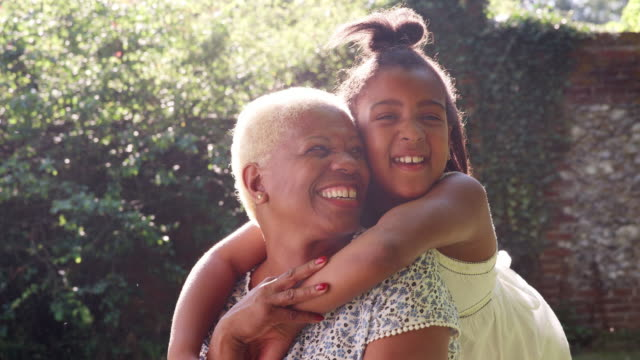 senior black woman and granddaughter sit embracing outside - happy family стоковые видео и кадры b-roll