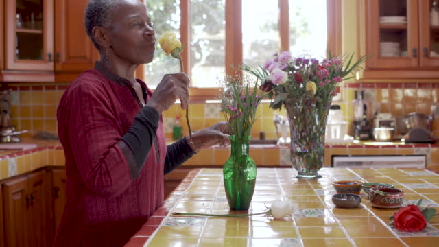 Senior black woman arranging flowers while listening to music in her kitchen Happy smiling senior African American black woman arranging and smelling flowers while listening to music in her kitchen baby boomers stock videos & royalty-free footage