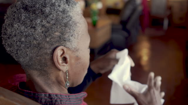 Senior black woman blowing her nose sick with an illness - OTS