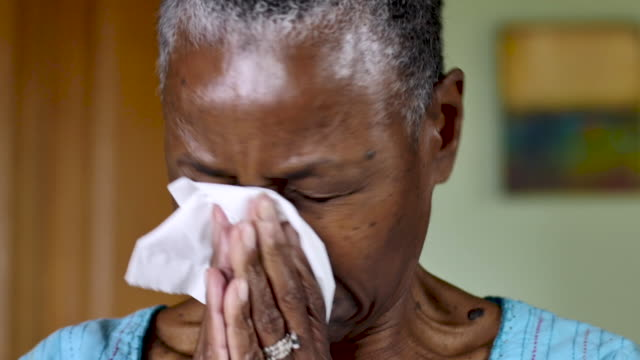Senior black woman blowing her nose with a facial tissue in her home