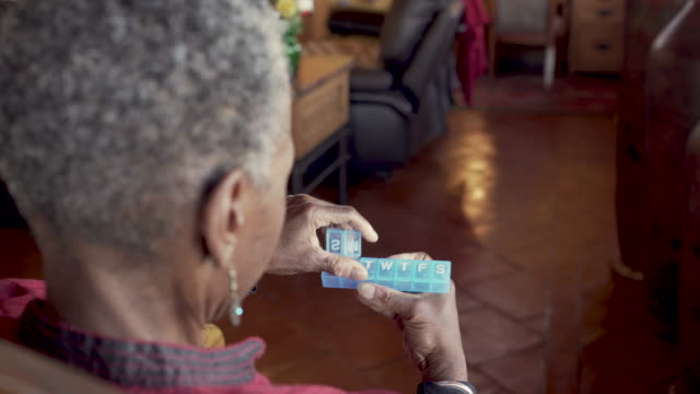 Senior black woman opening her daily pill planner - OTS Senior black woman opening her plastic daily pill planner preparing to add her medication, vitamins, and supplements for the week - over the shoulder medicare stock videos & royalty-free footage
