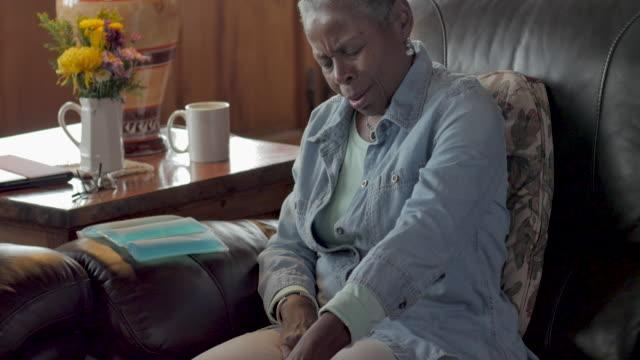 kıdemli siyah kadın ağrı rahatlatmak için dizine buz torbası koyarak - hayvan eklemi stok videoları ve detay görüntü çekimi