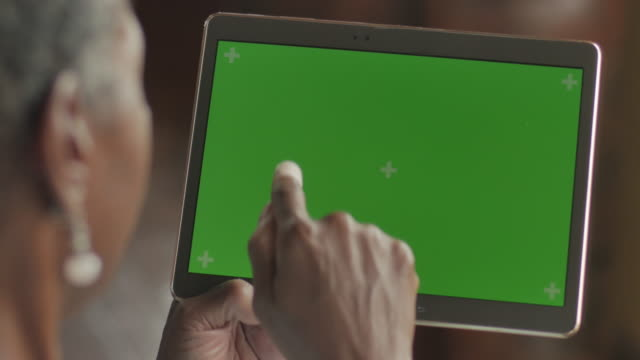 Senior black woman swiping and tapping a green screen digital tablet - OTS