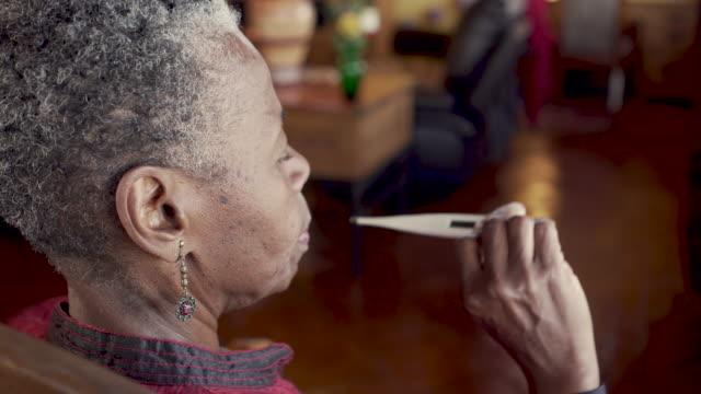stockvideo's en b-roll-footage met hogere zwarte vrouw die haar temperatuur met een digitale thermometer neemt - thermometer