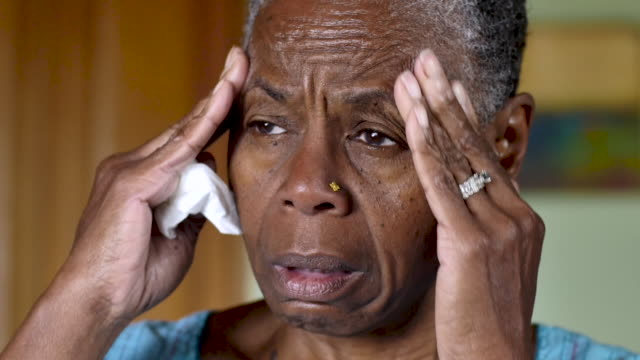 Senior black woman with an illness rubbing her temples and holding a tissue