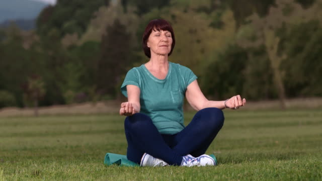 SLO MO Senior brunette woman meditating in the park video