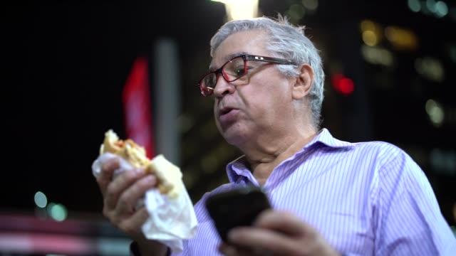 stockvideo's en b-roll-footage met senior business man hot dog eten op straat - ongezonde voeding