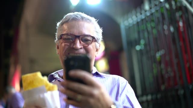 senior business-mann essen pastell auf der straße - brasilianische kultur stock-videos und b-roll-filmmaterial
