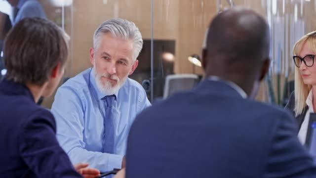 onun takım arkadaşları bir toplantıda dinlerken üst düzey iş adamı - klip uzunluğu stok videoları ve detay görüntü çekimi