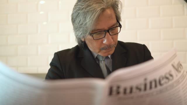 수석 비즈니스 남자 카페 커피숍에서 신문을 읽는. - 배경 초점 스톡 비디오 및 b-롤 화면