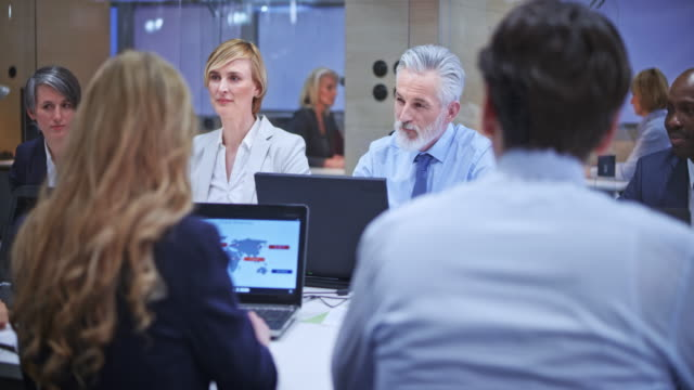 Senior business man with grey beard consulting his female colleague during the meeting in the conference room