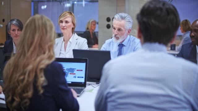 senior business man med grått skägg consulting hans kvinnliga kollega under mötet i konferensrummet - affärskonferens bildbanksvideor och videomaterial från bakom kulisserna