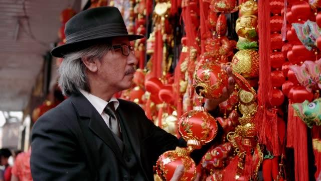 vídeos de stock e filmes b-roll de senior business men shopping chinese decorations - stock video - passagem de ano