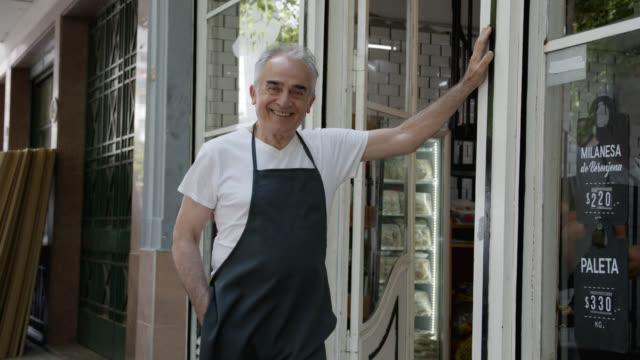 imprenditore senior di una macelleria appoggiando la mano contro il muro sorridendo alla telecamera - america latina video stock e b–roll
