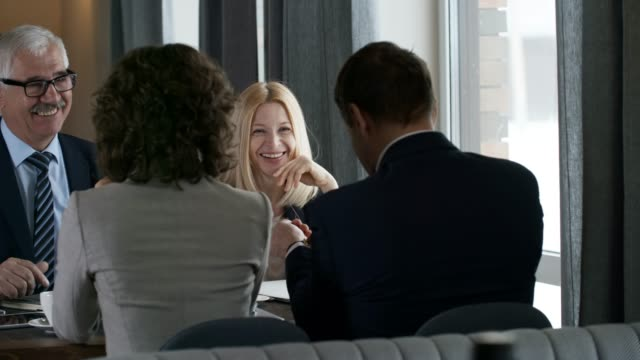 Senior Business Partners Smiling and Talking with Colleagues in Restaurant