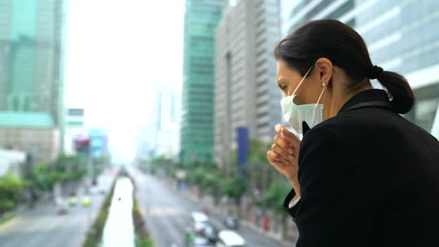 üst düzey iş kadını ile yüz maskesi koruma öksürük muzdarip. - maske stok videoları ve detay görüntü çekimi