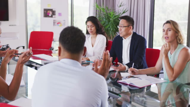 vídeos de stock e filmes b-roll de senior businessman discussing with young business people in meeting room in modern office - trabalho de design