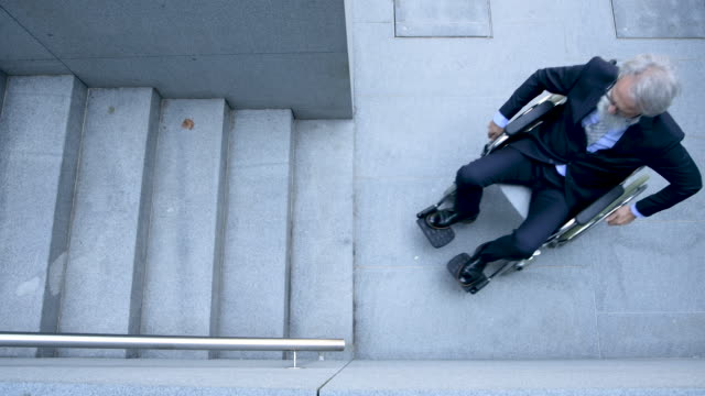 vídeos de stock, filmes e b-roll de homem de negócios sênior na cadeira de rodas - acessibilidade