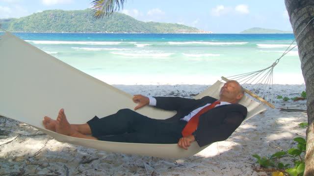 uomo d'affari senior rilassante in amaca sulla spiaggia tropicale - amaca video stock e b–roll