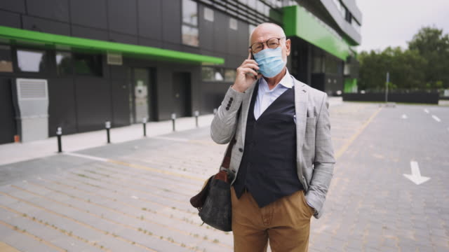 Senior businessman talking on a mobile phone while wearing protective mask video