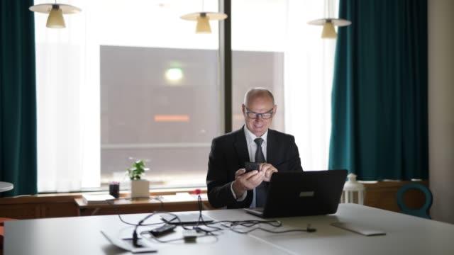 Homem de negócios sênior que usa o telefone e o portátil no escritório - vídeo