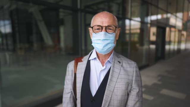 Senior businessman wearing protective mask video
