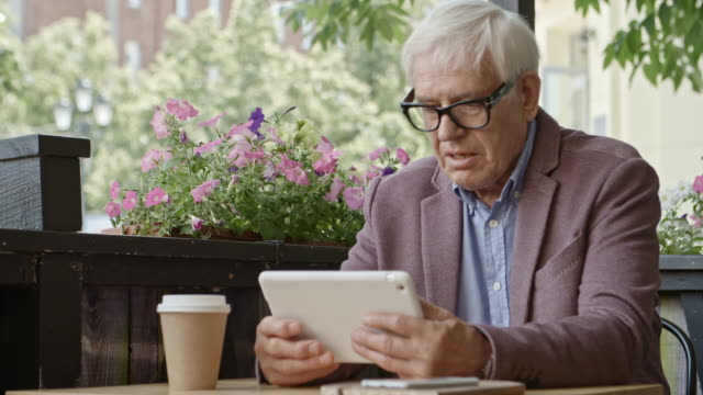 Senior Businessman Working on Tablet Over Coffee in Outdoor Restaurant video