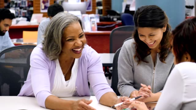 Senior businesswoman leads meeting with colleagues Confident senior African American businesswoman smiles while talking with female colleagues during a weekly staff meeting. They smile and laugh together while discussing business. mid adult stock videos & royalty-free footage