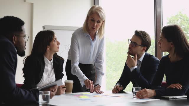 senior businesswoman mentor lehre junge arbeitnehmer erklären papierkram im büro - grundschullehrer stock-videos und b-roll-filmmaterial