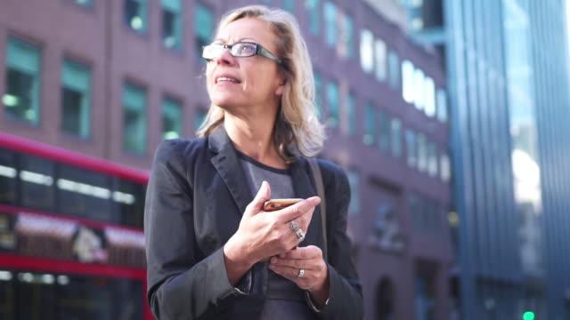 senior affärskvinna med hjälp av smart telefon i london - senior walking bildbanksvideor och videomaterial från bakom kulisserna