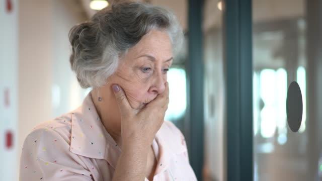 senior-geschäftsfrau besorgt über korridorbüro - weibliche angestellte stock-videos und b-roll-filmmaterial
