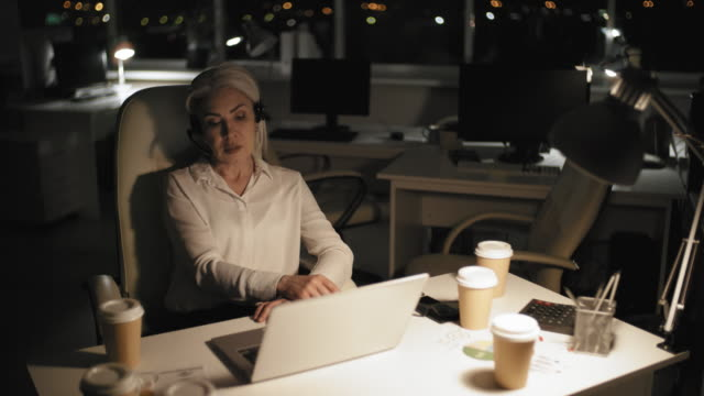 Senior Career Woman Having Conference Call Late at Night in Office