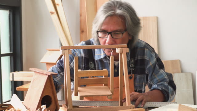senior carpenter check last components of wooden swing model in the workshop house