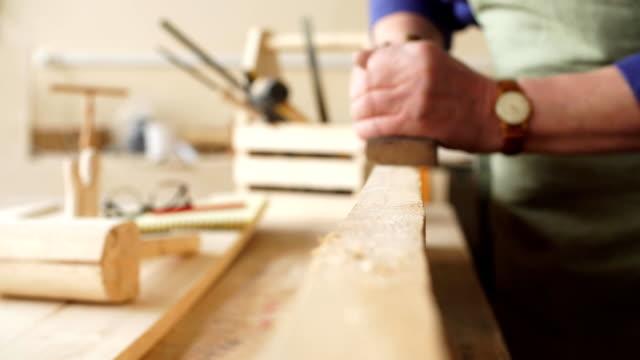 vídeos de stock e filmes b-roll de senior carpenter is smoothing the edge of wooden planks - material de construção