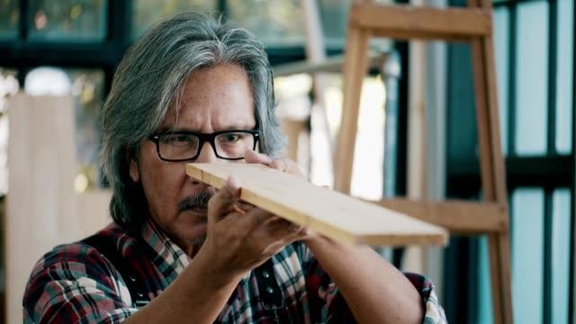 Charpentier principal regardant par le biais de vérifier le bois - Vidéo