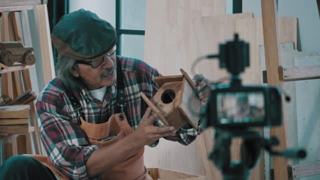 vidéos et rushes de homme principal de charpentier utilisant la caméra de ditital pour le streaming direct de vidéo - interview