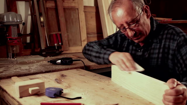 senior carpenter invio di un pezzo di legno con carta abrasiva - levigatrice video stock e b–roll