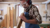 istock Senior carpenter wearing protective wear in his workshop and checking a piece of wood he just cut 1137346196