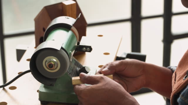 senior carpenter's hand removing wood corners by electric machine in the workshop house