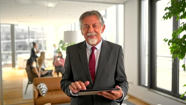 vídeos de stock e filmes b-roll de senior caucasian businessman using digital tablet in modern office - senior business woman tablet