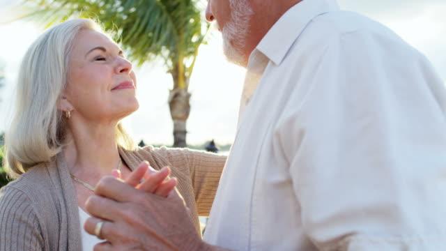 Senior Caucasian couple dancing together on Caribbean beach