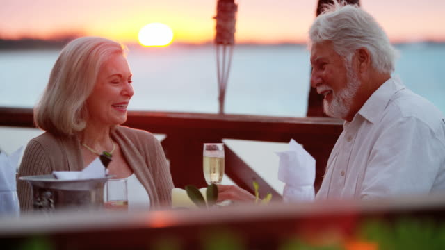 Senior Caucasian couple dining at tropical resort hotel