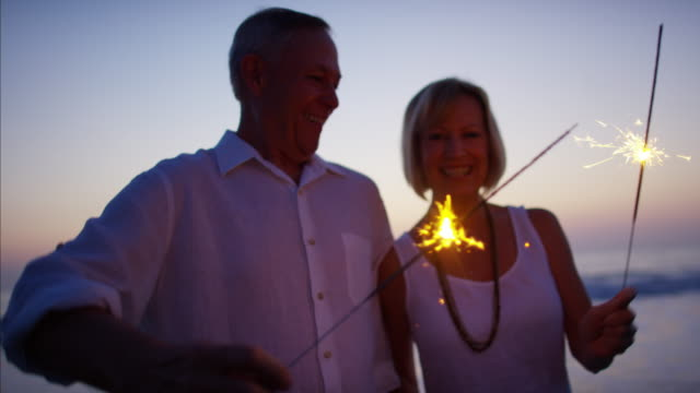 Senior Caucasian couple enjoying beach sunset with sparklers Senior mature Caucasian couple lifestyle travel resort healthcare dancing celebration sparklers beach sunset dusk RED DRAGON medicare stock videos & royalty-free footage